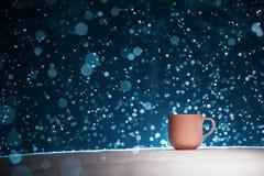 Tasse éclairée à contre-jour de café chaud sur le fond neigeux de nuit ; Images stock
