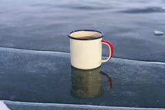 Tasse émaux avec le thé pour sur la glace bleue avec une fente dans le lac Baïkal en hiver Photos libres de droits