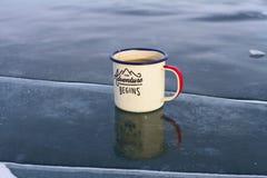 Tasse émaux avec le thé sur la glace bleue avec une fente dans le lac Baïkal un jour ensoleillé Images stock