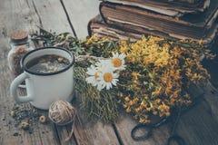 Tasse émaux de thé sain, groupes d'herbes médicinales et pile de vieux livres photo stock