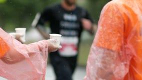 Tasse actuelle volontaire de fille avec de l'eau dans le point d'eau du marathon, dans l'athlète courant de fond banque de vidéos