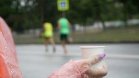 Tasse actuelle volontaire de fille avec de l'eau dans le point d'eau du marathon, dans l'athlète courant de fond clips vidéos