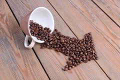 Tasse avec des grains de café sur une table en bois Photographie stock