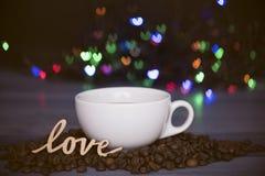 Tasse avec du café et des grains de café avec le symbole d'amour Images libres de droits