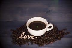Tasse avec du café et des grains de café avec le symbole d'amour Image libre de droits
