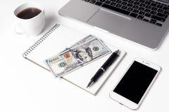 Tasse avec du café, le carnet sur lequel se trouvent deux cents dollars et S Photos libres de droits