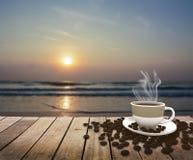 Tasse avec du café sur la table au-dessus de la mer au lever de soleil Photo stock