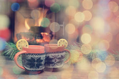 Tasse avec l'ornement de Noël près de la cheminée Tasse en m tricoté par rouge Photographie stock