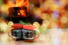 Tasse avec l'ornement de Noël près de la cheminée Tasse en tissu tricoté Photo stock
