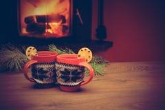 Tasse avec l'ornement de Noël près de la cheminée Tasse en tissu tricoté Image libre de droits