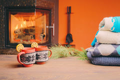 Tasse avec l'ornement de Noël près de la cheminée Tasse en tissu tricoté Photos stock