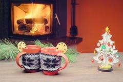 Tasse avec l'ornement de Noël près de la cheminée Vacances d'hiver Photo stock