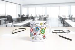 Tasse avec la copie de plan d'affaires et insigne sur la table en PS ouvert Photo stock