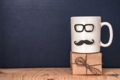 Tasse avec la moustache, verres, boîte-cadeau au-dessus de tableau noir, holi Photographie stock