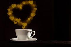 Tasse avec la vapeur d'or de forme de coeur d'imagination Image libre de droits