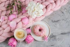 Tasse avec le cappuccino, beignet, couverture géante en pastel rose, fleurs images libres de droits