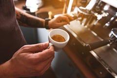 Tasse avec le cappuccino chaud dans des mains de l'homme Image stock