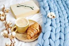 Tasse avec le cappuccino, croissant, plaid géant en pastel bleu image stock