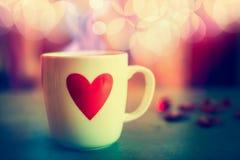 Tasse avec le coeur au fond de bokeh, vue de face Symbole d'amour ou jour de valentines Image stock