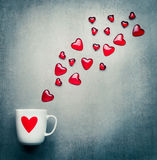 Tasse avec le coeur rouge et les coeurs en verre volants Symboles d'amour, jour de valentines ou concept romantique d'anniversair Photos stock