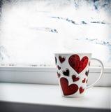 Tasse avec le coeur sur le filon-couche de fenêtre Image libre de droits