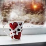 Tasse avec le coeur sur un filon-couche de fenêtre Photographie stock libre de droits
