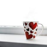 Tasse avec le coeur sur un filon-couche de fenêtre d'isolement Images stock
