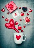 Tasse avec le symbole de coeur et décoration rouge de jour de valentines avec le boîte-cadeau, la carte de voeux, la serrure et l Image stock