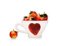 Tasse avec le symbole de St.Valentine et pommes de massepain d'isolement Photo libre de droits