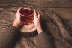 Tasse avec le thé dans les mains d'une fille photo stock