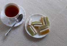 Tasse avec le thé et les bonbons Image stock