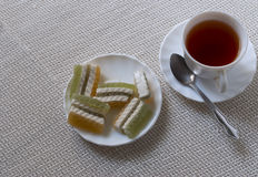 Tasse avec le thé et les bonbons Photo stock