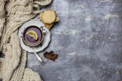 Tasse avec le thé noir et le citron et la soucoupe, la cuillère, la gelée dans le pot, les feuilles d'érable et l'écharpe tricoté photographie stock