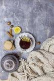Tasse avec le thé noir et le citron et la soucoupe, la théière, le citron, la noisette, les bâtons de la cannelle et l'écharpe tr photographie stock