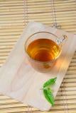 Tasse avec le thé vert et les feuilles. Image libre de droits