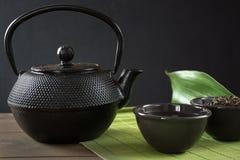 Tasse avec le thé vert avec la bouilloire noire de porcelaine sur le noir avec l'espace de copie Fin vers le haut Concept chinois Image stock