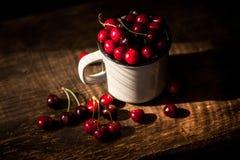Tasse avec les cerises rouges douces sur la table images stock