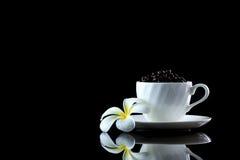 Tasse avec les grains de café et le frangipani sur un backgr réfléchi noir Photo libre de droits