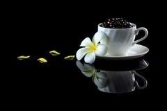 Tasse avec les grains de café et le frangipani sur un backgr réfléchi noir Images libres de droits