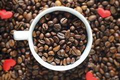 Tasse blanche avec des grains de café sur le fond de grains de café Images stock