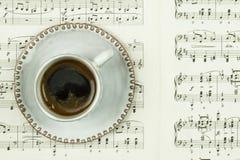 Tasse blanche avec du café noir et des pages avec les notes classiques de musique comme fond en tant qu'heure pour le café et le  images stock