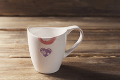 Tasse blanche avec le coeur et le rouge à lèvres peints, jour du ` s de Valentine, sur le fond de vieilles planches en bois Photographie stock libre de droits