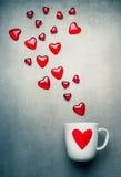 Tasse blanche avec le coeur rouge et les coeurs en verre volants Symboles d'amour et concept de jour de valentines Photographie stock libre de droits