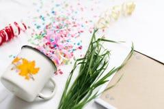 Tasse blanche avec le mocap de fête d'isolat de confettis Images stock