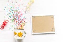 Tasse blanche avec le mocap de fête d'isolat de confettis Photos stock