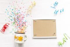 Tasse blanche avec le mocap de fête d'isolat de confettis Photographie stock libre de droits