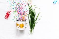 Tasse blanche avec le mocap de fête d'isolat de confettis Image stock