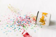 Tasse blanche avec le mocap de fête d'isolat de confettis Photo stock