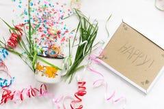 Tasse blanche avec le mocap de fête d'isolat de confettis Photos libres de droits