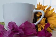 Tasse blanche avec le tournesol et les fleurs roses photos stock